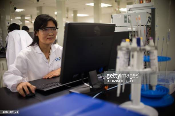 A worker of the US Pharmacopeial Convention company works in the company's laboratory in the China Pilot Free Trade zone during a media trip on...