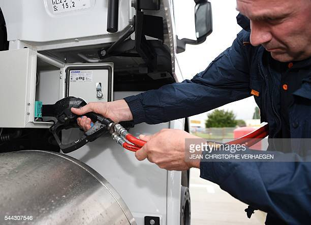 A worker of Transalliance fills up a truck with compressed natural gas at the gas station of Air Liquide on June 28 2016 in FlévilledevantNancy...