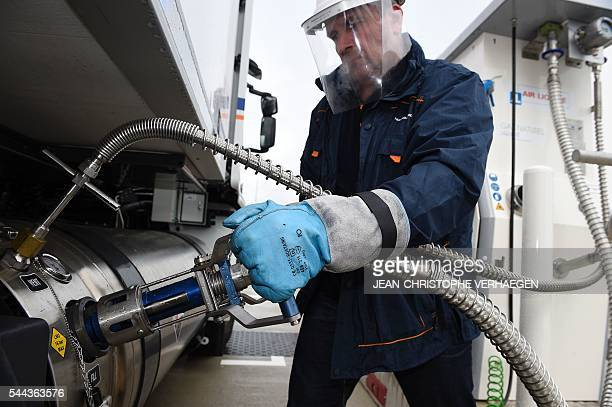 A worker of Transalliance fills up a truck with liquefied natural gas at the gas station of Air Liquide on June 28 2016 in FlévilledevantNancy...