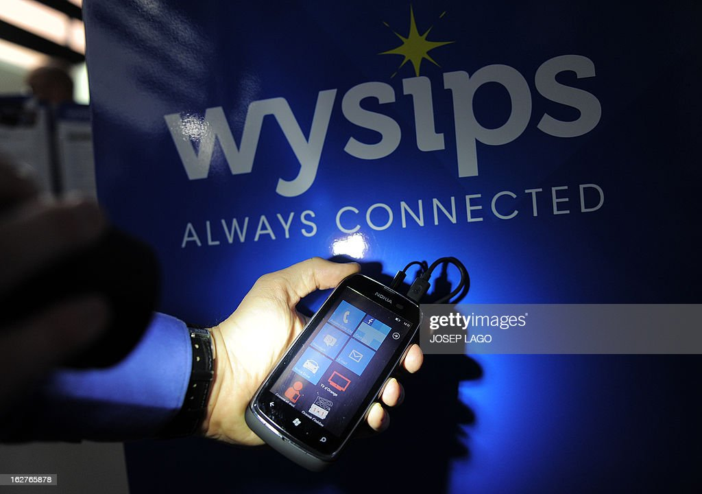 A worker of Wysips shines a torch on the screen of a prototype of a smartphone equipped with a photovoltaic film at the 2013 Mobile World Congress in Barcelona on February 26, 2013. A transparent film that costs just one euro (1.30 USD) to make could bring an end to the anguish of mobile phone users facing the dreaded dead-battery message. Wysips, a startup based in Aix-en-Provence, southern France, has developed a photovoltaic film which can be built seamlessly into a mobile phone screen and deliver the joy of life to a flat battery.