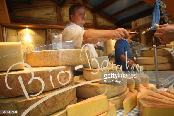 A worker offers a visitor a sample of organic mountain cheese at a stand at the Gruene Woche agricultural trade fair January 18 2008 in Berlin...