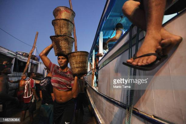 A worker offloads baskets of acai berry at the historic VeroPeso market at dawn on June 7 2012 in Belem Brazil Belem is considered the entrance gate...