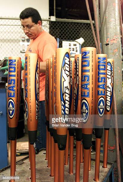 A worker on a baseball bat assembly line stacks aluminum bats at Easton Sports in Van Nuys Tuesday after joining two pieces of aluminum stock DIGITAL...