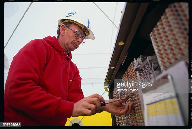 A worker on a Bell Atlantic project to provide video dial tone repairs fiber optic cables | Location Dover New Jersey USA