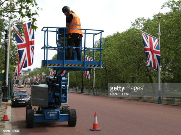 A worker on a cherrypicker installs loud speakers on The Mall in central London on June 8 as Britain prepares to celebrate the 90th birthday of Queen...