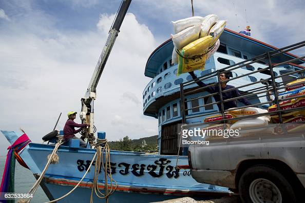 A worker on a ferry uses a crane to move bags of rice on to the back of a pickup truck in Koh Phangan Surat Thani Thailand on Wednesday Jan 18 2017...