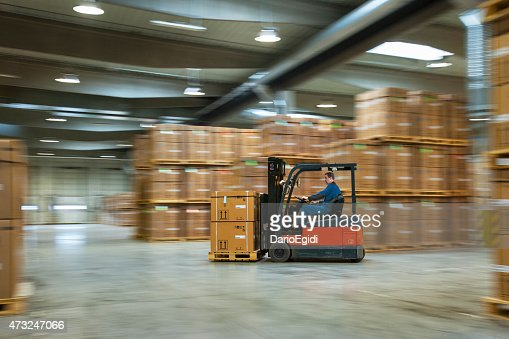 Worker on a lift truck arranging boxes in industrial warehouse