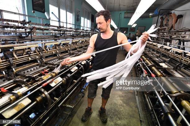 worker on a machine manufactures silk stockings and underwear in the society of Arsoie on September 7 2017 in Sumène in the southern France / AFP...