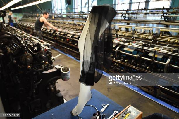 worker on a machine manufactures silk stockings in the society of Arsoie on September 7 2017 in Sumène in the southern France / AFP PHOTO / Pascal...