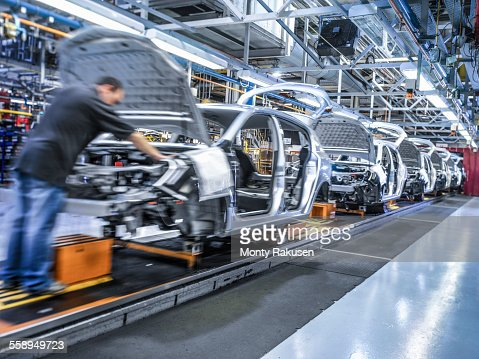 Worker on car production line in car factory