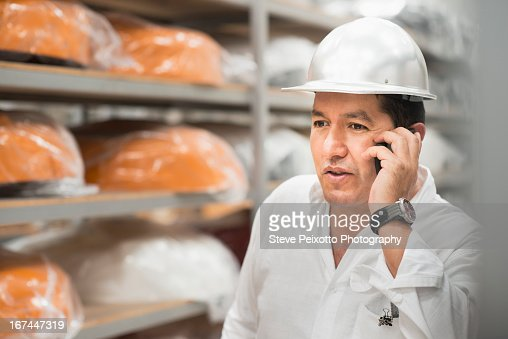 Worker on cell phone in manufacturing plant : Stock Photo