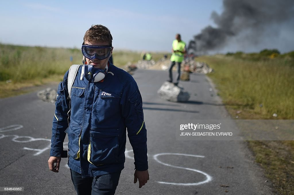 A worker on strike walks next to a fire barricade to block the access to an oil depot near the Total refinery of Donges, western France, to protest against the government's planned labour law reforms, on May 27, 2016. The French government's labour market proposals, which are designed to make it easier for companies to hire and fire, have sparked a series of nationwide protests and strikes over the past three months. French unions on May 27 called on workers to 'continue and step up their action', as a wave of strikes against a disputed labour law disrupted transport and fuel supplies. / AFP / JEAN