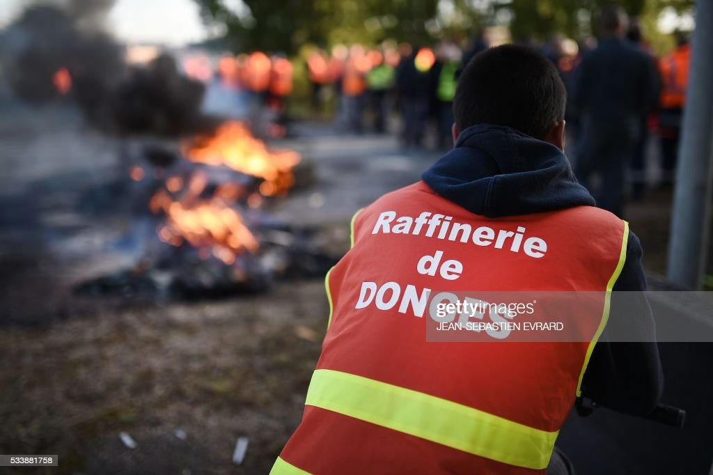 A worker on strike, wearing working clothes of the Donges refinery, blocks the access to the harbour of Saint-Nazaire, western france, on May 24, 2016 to protest against the government's planned labour law reforms. Petrol shortages caused long tailbacks of motorists in parts of France on May 23 as protesters angry over government labour reforms blockaded some of the country's oil refineries and fuel depots. The action was the latest in three months of strikes and protests against the reform, which has set the Socialist government against some of its traditional supporters and sometimes sparked violence. / AFP / JEAN