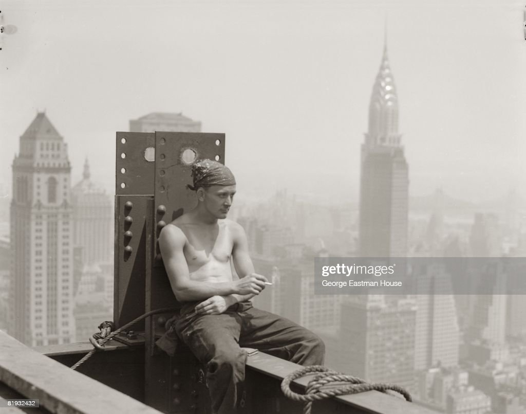 A worker on the construction of the Empire State Building enjoys a quiet time high up on the scaffolding, 1931, New York, United States