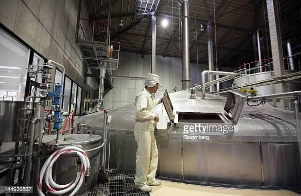 A worker opens a mash tun at Suntory Holdings Ltd's Hakushu distillery in Hokuto City Yamanashi Prefecture Japan on Monday May 21 2012 Suntory...