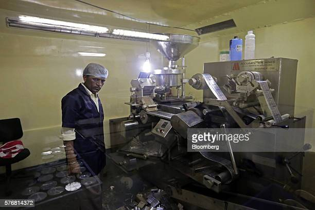 A worker operates a blister packing machine at the factory of Jain's Cow Urine Therapy Health Clinic in Indore Madhya Pradesh India on Monday June 27...