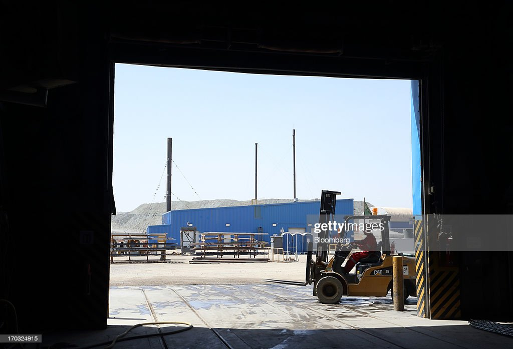 A worker operates a Caterpillar Inc. forklift outside the No. 1 shaft building at the Oyu Tolgoi copper-gold mine, jointly owned by Rio Tinto Group's unit Turquoise Hill Resources Ltd. and Erdenes Oyu Tolgoi LLC, in Khanbogd, the South Gobi desert, Mongolia, on Friday, June 7, 2013. Rio Tinto, the world's second-biggest mining company, is expected to start first shipments from its $6.6 billion copper-gold mine in Mongolia this month. Photographer: Tomohiro Ohsumi/Bloomberg via Getty Images