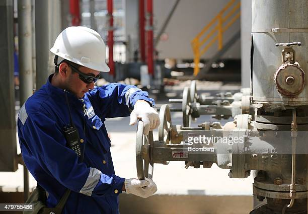 A worker operates a control valve on pipework at the Atyrau oil refinery operated by KazMunaiGas National Co in Atyrau Kazakhstan on Thursday July 2...