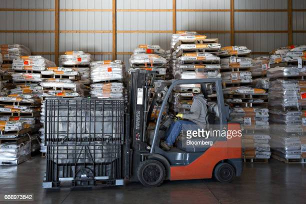 A worker operates a forklift in front of bags of DuPont Co Pioneer brand corn seed at the MJ Seed Inc facility in Manlius Illinois US on Friday April...