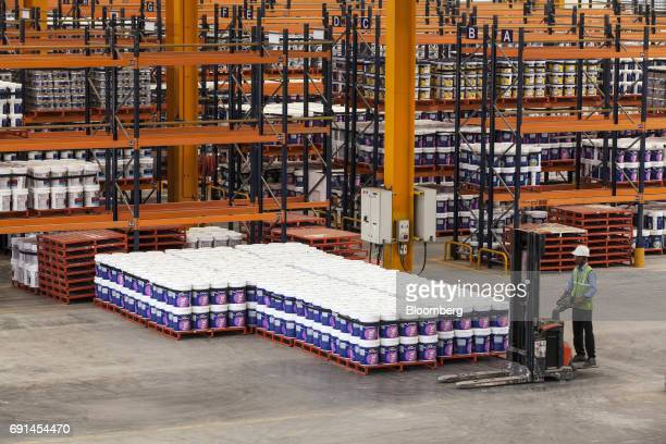 A worker operates a forklift past buckets of Dulux branded paint inside a warehouse at an Akzo Nobel India Ltd factory in Gwalior Madhya Pradesh...