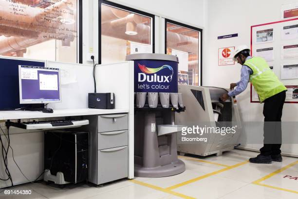 A worker operates a gyro mixer that blends Dulux branded paints at an Akzo Nobel India Ltd paint factory in Gwalior Madhya Pradesh India on Thursday...