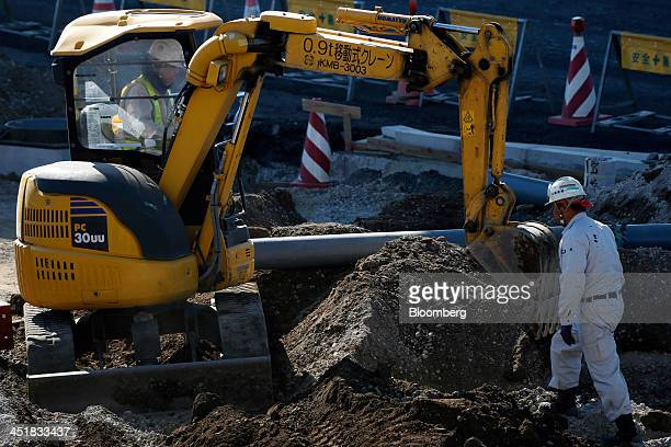 A worker operates a Komatsu Ltd excavator as another worker walks through a construction site in Tokyo Japan on Friday Nov 22 2013 Monthly capital...