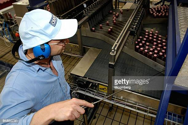 A worker operates a machine on the Campari Soda production line at the Campari factory in Novi Ligure Italy on Tuesday April 22 2008 Davide...