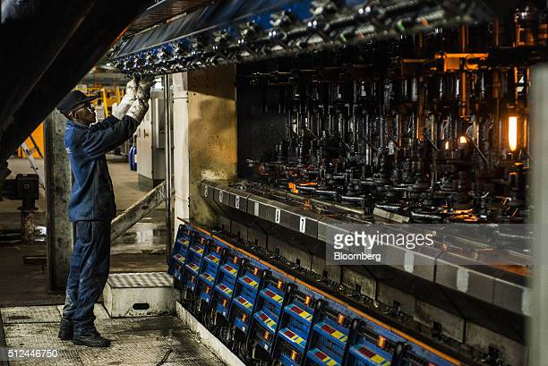 A worker operates a machine used to mold clear glass bottles at the Nampak Ltd manufacturing plant in Roodekop South Africa on Friday Feb 26 2016...