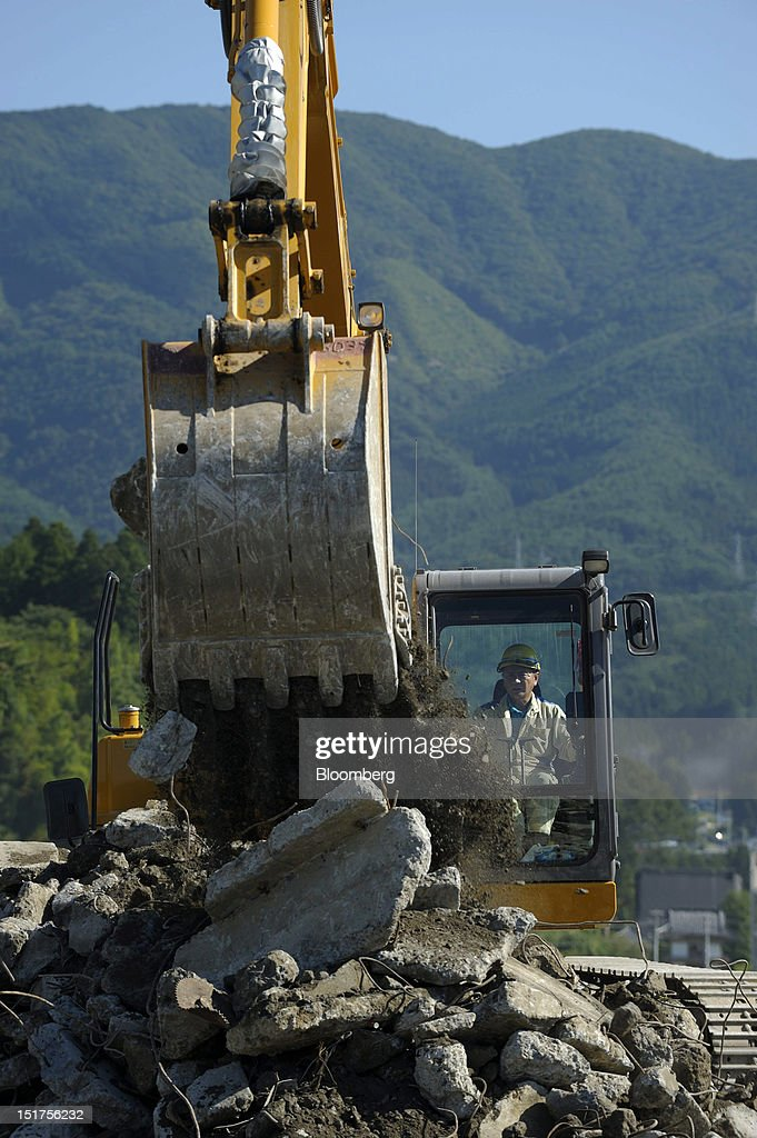 A worker operates an excavator in an area damaged by last year's March 11 earthquake and tsunami in Rikuzentakata City, Iwate Prefecture, Japan, on Friday, Sept. 7, 2012. Japan's economy expanded in the second quarter at half the pace the government initially estimated, underscoring the risk of a contraction as Europe's debt crisis caps exports.Photographer: Akio Kon/Bloomberg via Getty Images
