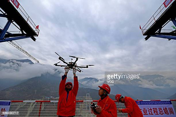 YA'AN CHINA DECEMBER 20 A worker operates an unmanned aerial vehicle during the construction of the Ya'anKangding expressway bridge on December 20...