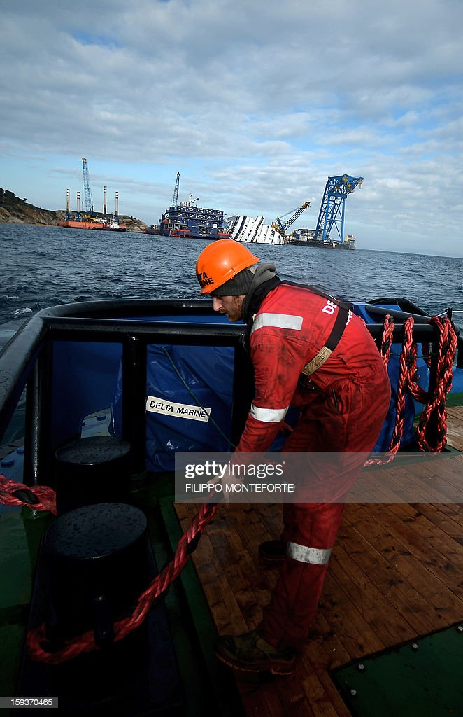 A worker operates on a platform boat in front of the Costa Concordia cruise ship laying aground by the port the Italian island of Isola del Giglio on January 12, 2013. A year on from the Costa Concordia tragedy in which 32 people lost their lives, the giant cruise ship still lies keeled over on an Italian island and its captain Francesco Schettino has become a global figure of mockery. AFP PHOTO / FILIPPO MONTEFORTE