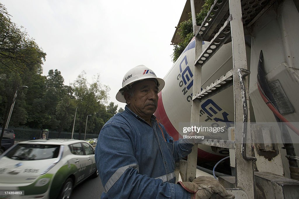 A worker operates the controls on a truck for pouring Cemex SAB concrete to a conveyor bucket during construction of a building in Mexico City, Mexico. on Friday, July 19, 2013. Mexican President Enrique Pena Nietos $320 billion infrastructure plan is reviving a rally in cement maker Cemex SABs bonds after the emerging-market rout derailed an advance fueled by the U.S. housing rebound. Photographer: Susana Gonzalez/Bloomberg via Getty Images