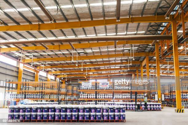 A worker operating a forklift drives past buckets of Dulux branded paint inside a warehouse at an Akzo Nobel India Ltd factory in Gwalior Madhya...