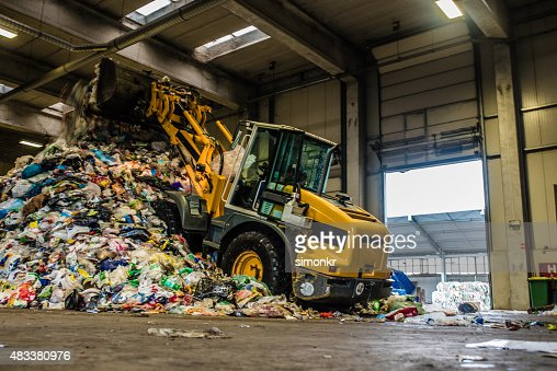 Worker operating bulldozer at recycling plant