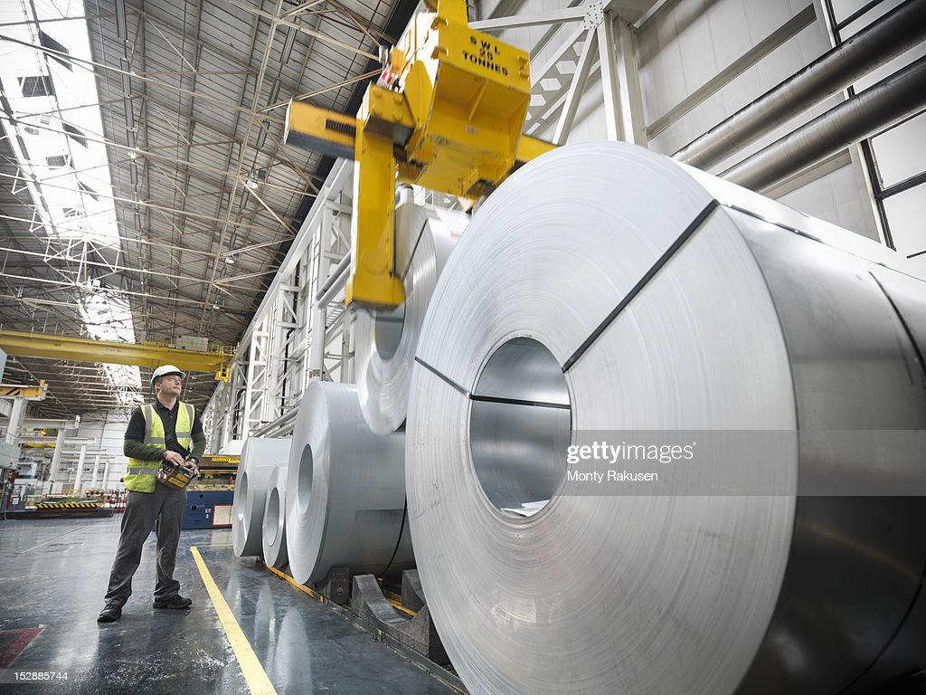 Worker operating crane with steel rolls in car factory
