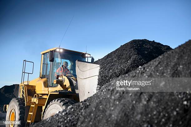 Worker operating digger with pile of coal at surface coal mine