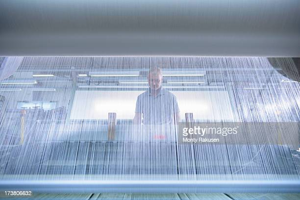 Worker operating industrial loom in textile mill