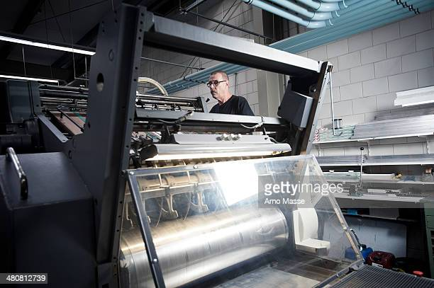 Worker operating printing machine in print workshop