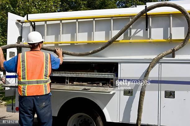 Worker operating water main break at truck, rear view