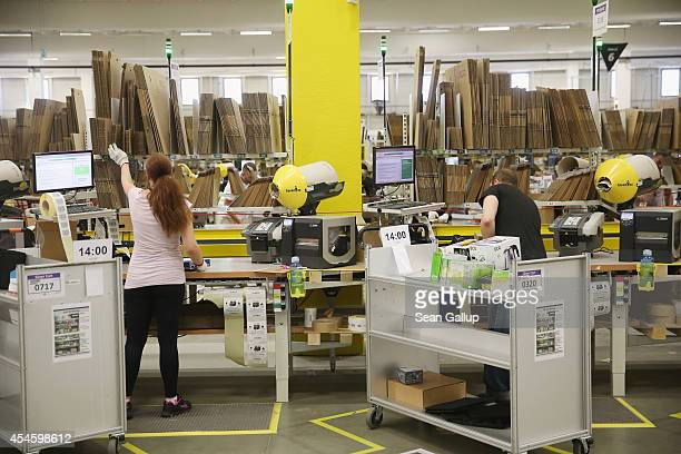 Worker pack orders at an Amazon warehouse on September 4 2014 in Brieselang Germany Germany is online retailer Amazon's second largest market after...