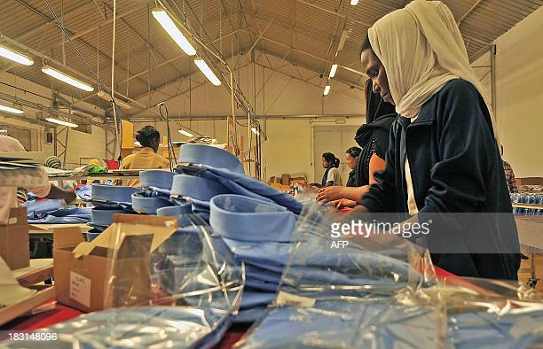 A worker packages dress shirts on the assembly floor at the Dolce Vita textile factory in Asmara on July 16 2013 The Italianowned factory is one of...