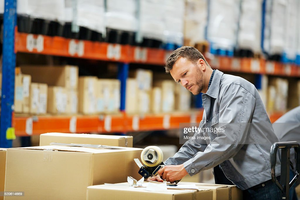Worker packing cardboard box in warehouse