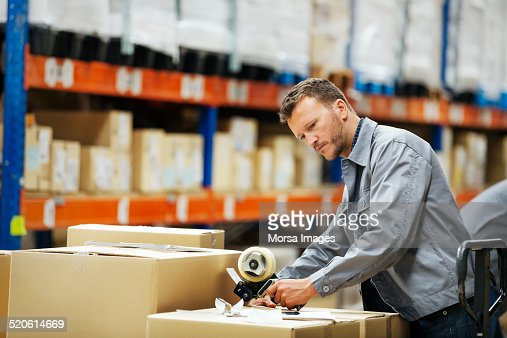 Worker packing cardboard box in warehouse