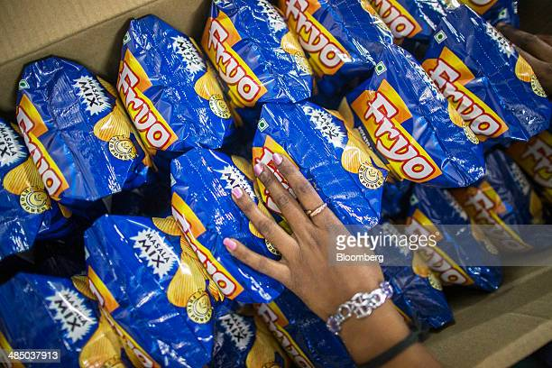 A worker packs bags of Fryo Foods Pvt Masala Mix crinklecut potato chips into a box at the company's factory in Meerut Uttar Pradesh India on Monday...