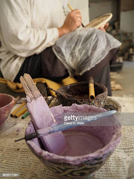 Worker painting bowl