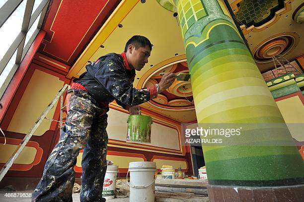 A worker paints a column in the function room of a building built in neoAndean baroque architecture known as Cholet style in El Alto Bolivia taken on...