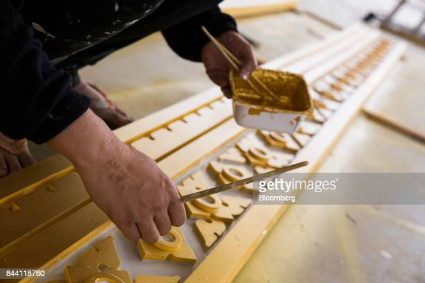A worker paints a decoration while preparing the ceremonial ground for King Bhumibol Adulyadej's cremation at Sanam Luang park in Bangkok Thailand on...