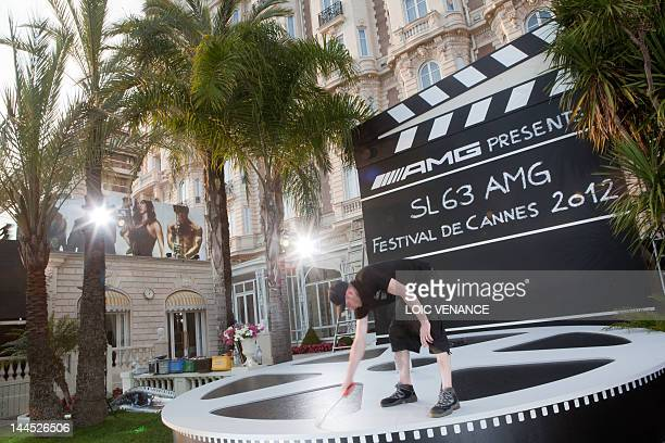 A worker paints an advertisement in form of a clap in front of the Carlton hotel on tow days before the 65th Cannes film festival on May 14 2012 near...