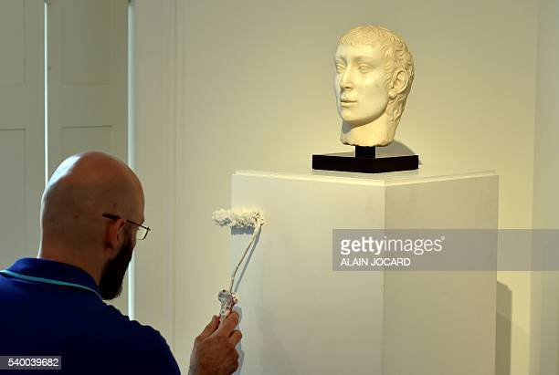 A worker paints the display stand under a white marble head of John the Baptist probably by Gregorio di Lorenzo circa 1460/70 estimated 80000100000...