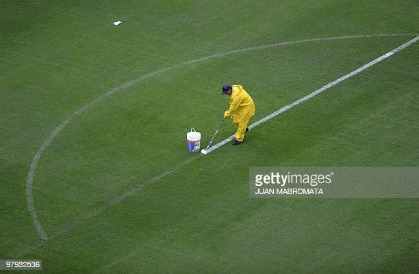 A worker paints the lines of Boca Juniors' field before the start of Argentina's first division Boca vs River Plate football match under heavy rain...